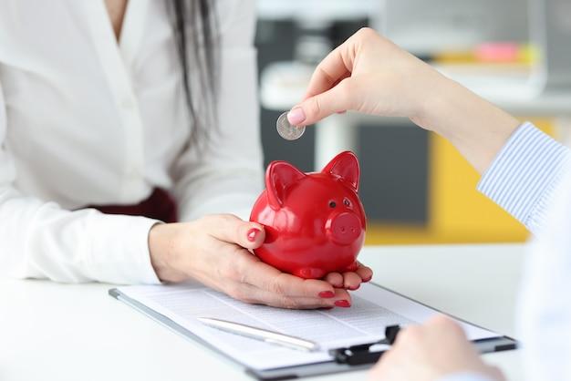Vrouwelijke hand zilveren munt ingebruikneming rode spaarvarken close-up bedrijfsconcept investeringen