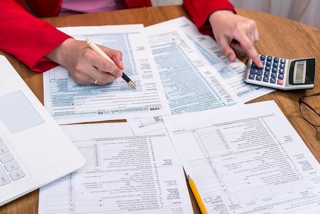 Vrouwelijke handen 1040 formulier invullen en berekenen in kantoor