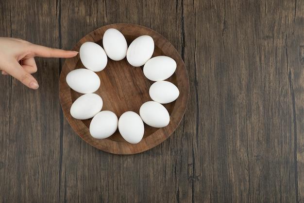 Vrouwelijke handen aanraken van houten bord met rauwe eieren op houten oppervlak.