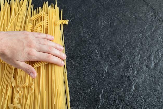Vrouwelijke handen aanraken van verschillende pasta op donkere ondergrond.