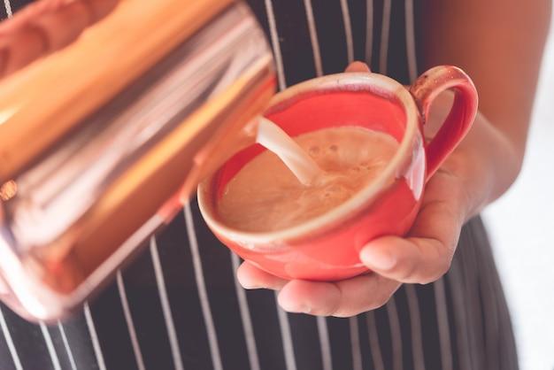 Vrouwelijke handen barista bedrijf en gieten melk voor latte kunst in rode beker