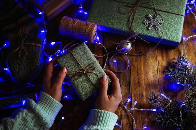 Vrouwelijke handen bereiden cadeaus voor kerstmis op houten tafel