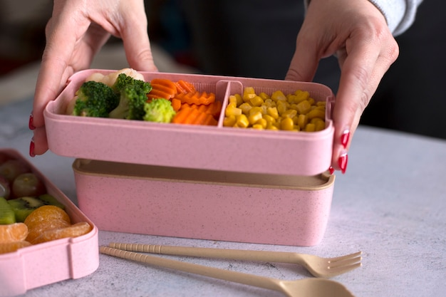 Vrouwelijke handen bereiden een container met voedsel voor. meisje die lunch voor het werk in lunchdoos maken
