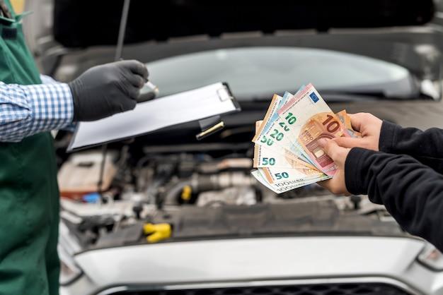 Vrouwelijke handen betalen voor autoservice aan werknemer