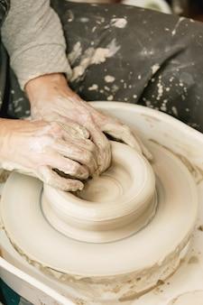 Vrouwelijke handen bezig met aardewerk wiel