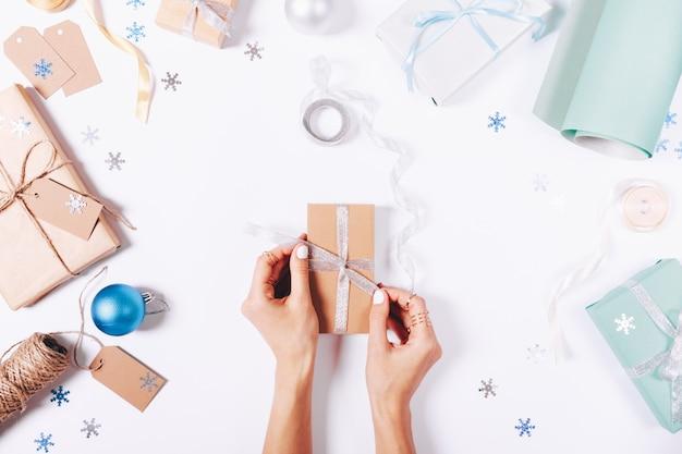 Vrouwelijke handen binden een lint op een doos met een geschenk