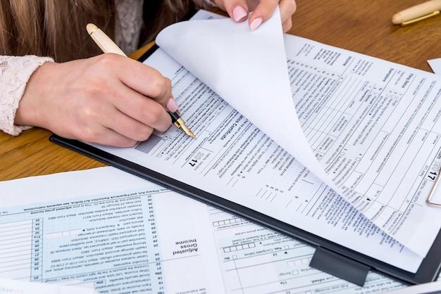 Vrouwelijke handen die 1040-formulier invullen, belastingconcept