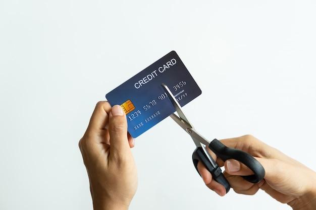 Vrouwelijke handen die creditcard met schaar snijden