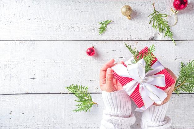 Vrouwelijke handen die de doos van de kerstmisgift houden