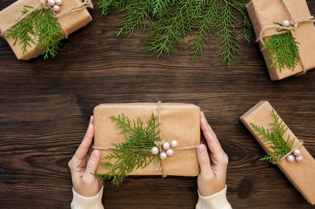 Vrouwelijke handen die de doos van de kerstmisgift op donker hout houden