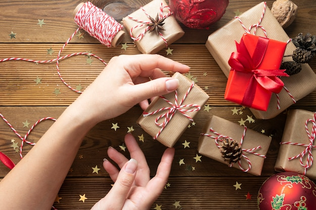 Vrouwelijke handen die, de doos van de kerstmisgift verpakken.