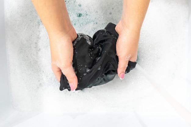 Vrouwelijke handen die de kleren van de zwarte kleurenzijde in bassin wassen