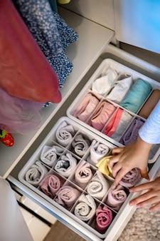 Vrouwelijke handen die de opslag van ondergoed, sokken, t-shirts organiseren, gebruiken de marie kondos-methode perfectionistische te...