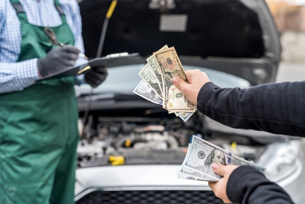 Vrouwelijke handen die dollarbankbiljetten geven aan monteur