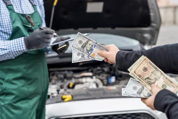 Vrouwelijke handen die dollarbankbiljetten geven aan werktuigkundige