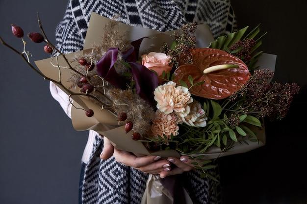 Vrouwelijke handen die een boeket houden dat in uitstekende stijl op een donkere achtergrond wordt verfraaid