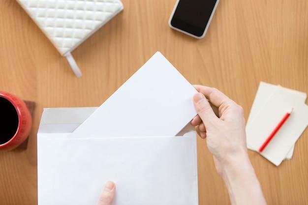 Vrouwelijke handen die een envelop met een vel over het kantoor houden