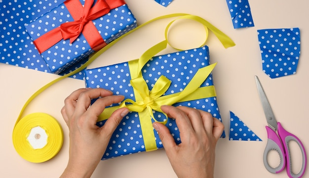 Vrouwelijke handen die een gele zijden strik op een blauwe geschenkdoos binden, een verrassing voorbereiden, bovenaanzicht