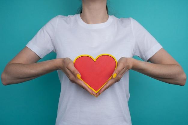 Vrouwelijke handen die een hartvorm vasthouden en aanbieden. liefde, gezondheidsconcept. selectieve aandacht.