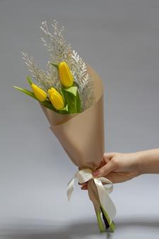 Vrouwelijke handen die een minimalistisch lenteboeket van ongebloeide gele tulpen houden en conferen, selectieve nadruk