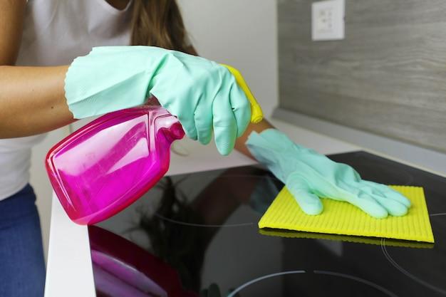 Vrouwelijke handen die een moderne zwarte inductiekookplaat schoonmaken met een doek en een spray.