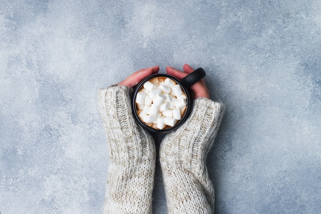 Vrouwelijke handen die een mok met hete chocolade en heemst op grijs houden