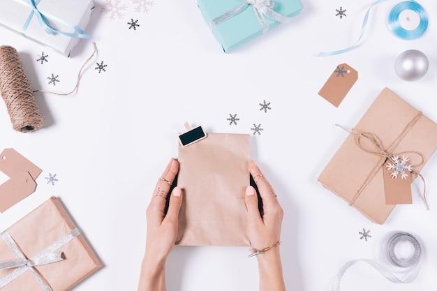 Vrouwelijke handen die een pakket met een gift onder kerstmisdecoratie houden