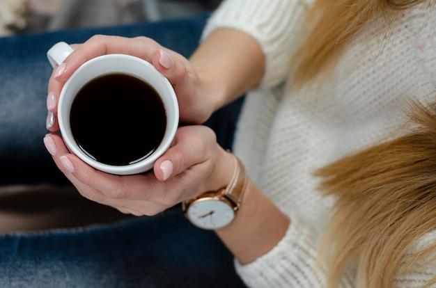 Vrouwelijke handen die een witte mok met drank houden. levensstijl concept. bovenaanzicht. detailopname