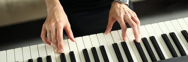 Vrouwelijke handen die elektrische piano thuis spelen