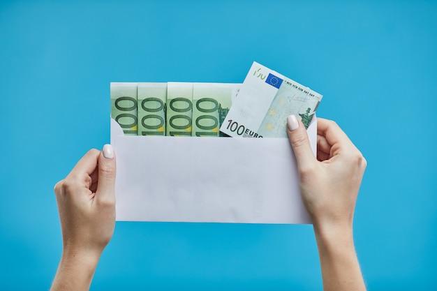 Vrouwelijke handen die euro bankbiljetten in een envelop houden