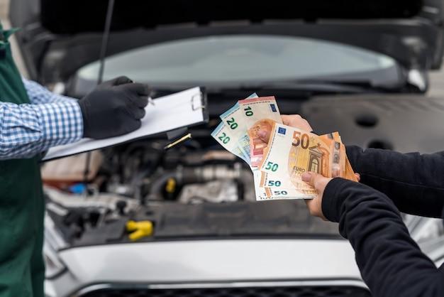 Vrouwelijke handen die eurobankbiljetten geven voor autoservice