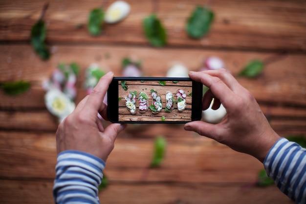 Vrouwelijke handen die foto van smakelijke sandwiches nemen