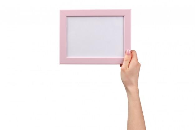 Vrouwelijke handen die fotoframe met exemplaarruimte houden die op wit wordt geïsoleerd
