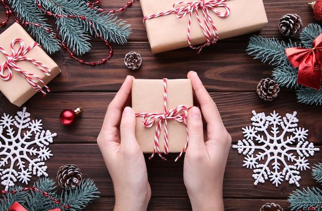Vrouwelijke handen die giftvakje op bruine houten lijst houden