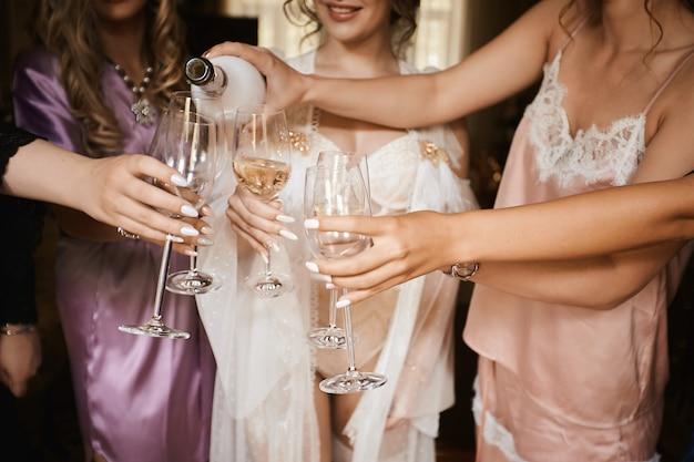 Vrouwelijke handen die glazen champagne houden bij kippenpartij. bruid en bruidsmeisjes roosteren met champagne en plezier op de huwelijksochtend. sluit omhoog foto van meisjes die een vrijgezellenfeest vieren.