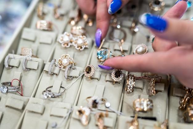 Vrouwelijke handen die gouden juwelen in winkel tonen