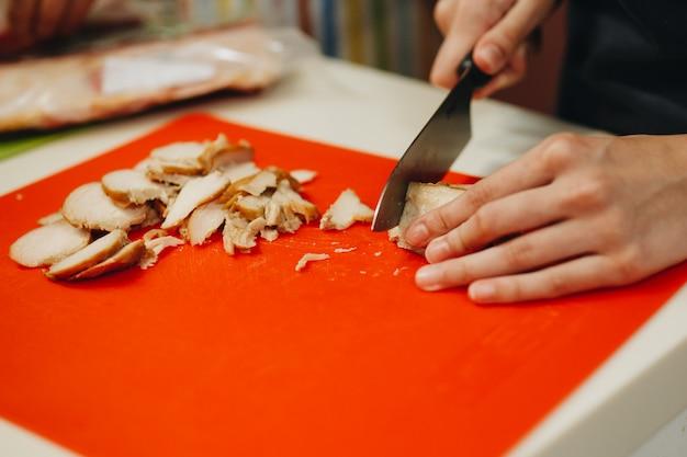 Vrouwelijke handen die groenten op een houten raad hakken