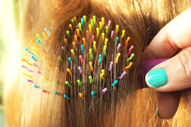 Vrouwelijke handen die het lange gouden haar van een meisje in de zon kammen.