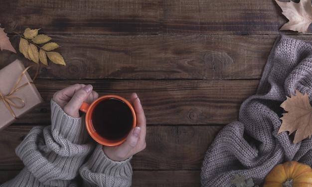 Vrouwelijke handen die hete koffie op houten achtergrond houden