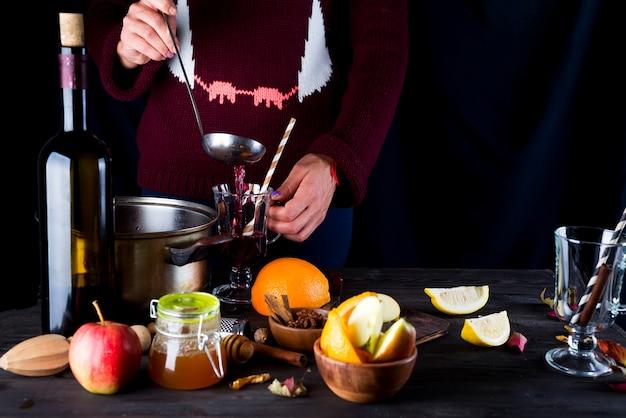 Vrouwelijke handen die hete overwogen wijn gieten