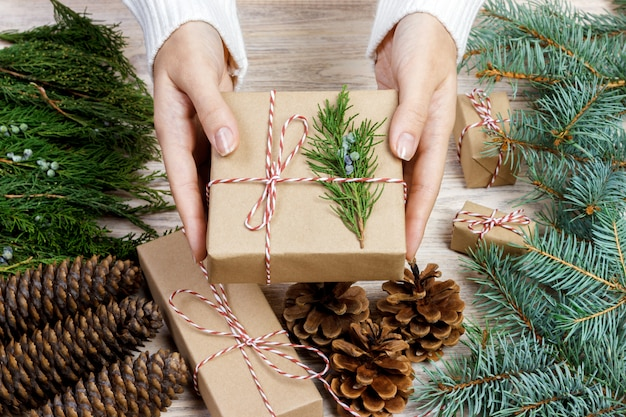 Vrouwelijke handen die kerstmisgiften verpakken in papier en hen verbinden met rode draden