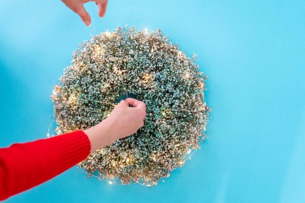 Vrouwelijke handen die kerstmiskroon met slinger verfraaien, hoogste mening