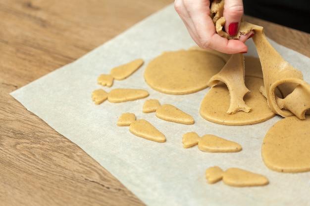 Vrouwelijke handen die koekjes ruw deeg maken