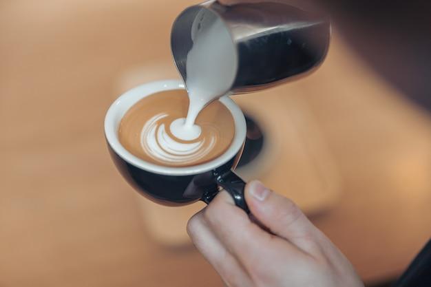 Vrouwelijke handen die koffie met melk versieren en latte art maken