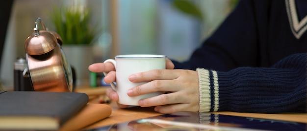 Vrouwelijke handen die koffiekop op houten huisbureau houden met programmaboeken, levering en decoratie