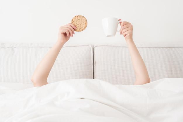 Vrouwelijke handen die kop van koffie en koekje boven deken in bed houden. vrouw die ontbijt in de ochtend heeft