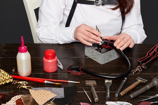Vrouwelijke handen die leren handvat voor handtas maken