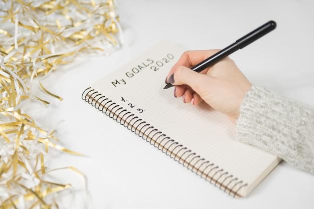 Vrouwelijke handen die mijn doelstellingen 2020 schrijven in een notitieboekje. klatergoud, nieuwjaar concept