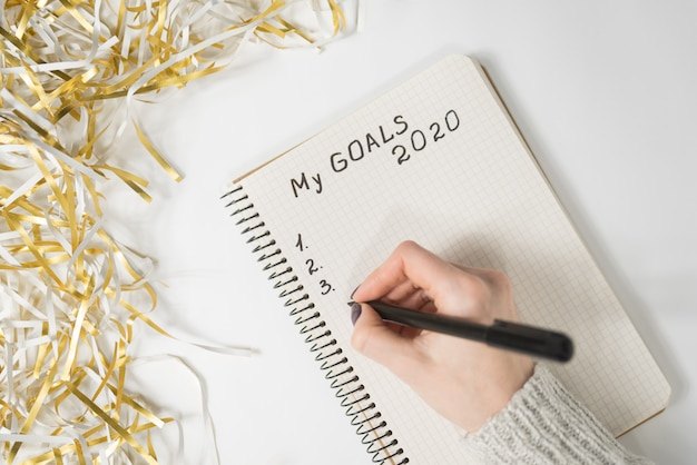 Vrouwelijke handen die mijn doelstellingen 2020 schrijven in een notitieboekje, klatergoud, nieuwjaarconcept