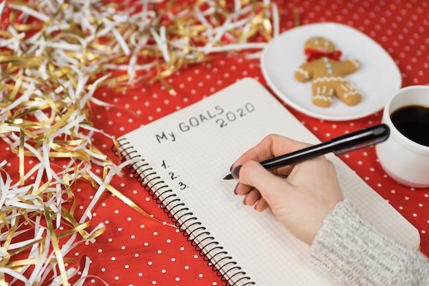 Vrouwelijke handen die mijn doelstellingen 2020 schrijven in een notitieboekje. speculaaspop, koffie, rood en klatergoud. nieuw jaars